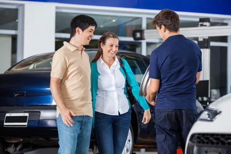 alloy: Happy couple discussing over alloy with mechanic at garage