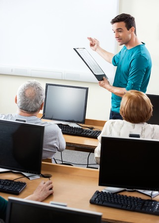 Young male tutor giving lessons to senior students in compute lab