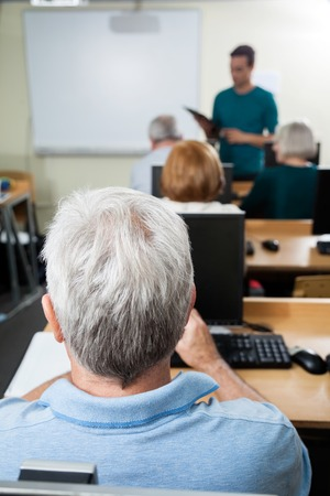 the elderly tutor: Senior student with male teacher in computer class Stock Photo