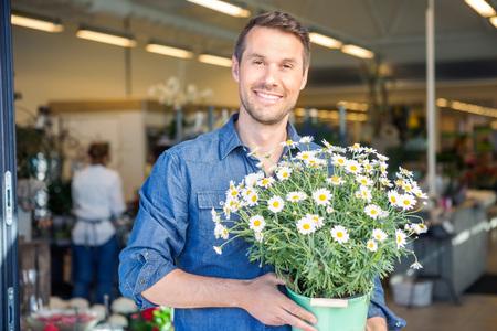 Ritratto di maschio felice piante cliente partecipazione fiorite in negozio photo
