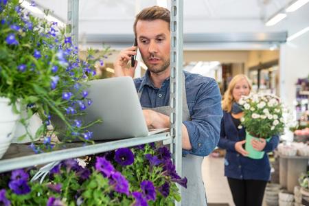 fiorista maschio utilizzando il telefono cellulare e computer portatile con il cliente che trasportano pianta in vaso in background presso il negozio photo
