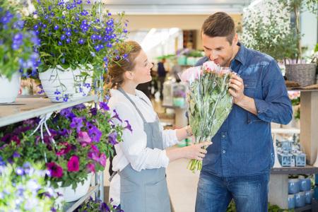 Fiorista dando cliente maschio di odore bouquet di fiori freschi in negozio photo