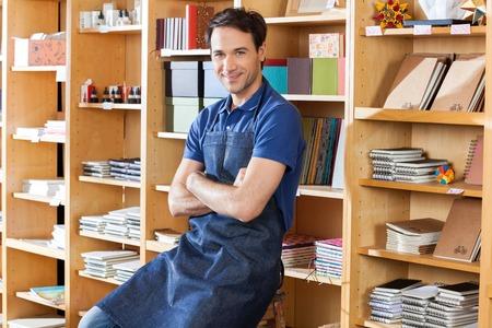 Ritratto di sorridere metà commesso degli adulti con le braccia incrociate seduto in negozio di libri photo