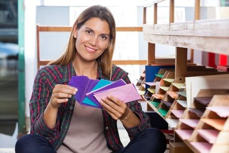 envelops: Portrait of smiling female customer holding envelops by shelves in store Stock Photo