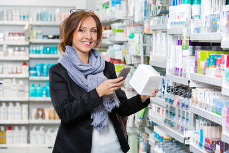 retail store: Portrait of smiling female customer scanning product through smart phone in pharmacy