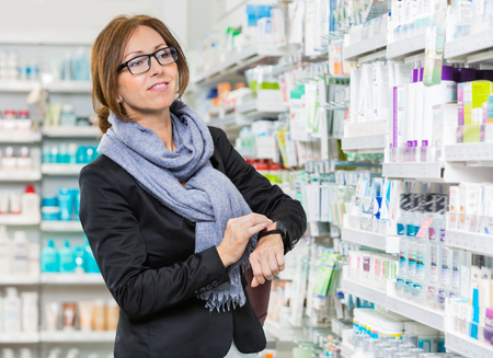 mid adult female: Mid adult female customer wearing smartwatch while looking at products in pharmacy