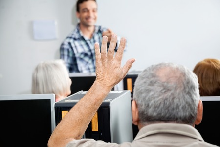 the elderly tutor: Senior man asking question while tutor explaining in computer class