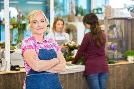Ritratto di fiducia fiorista femminile maturo con il collega che assiste clienti in fondo al negozio photo