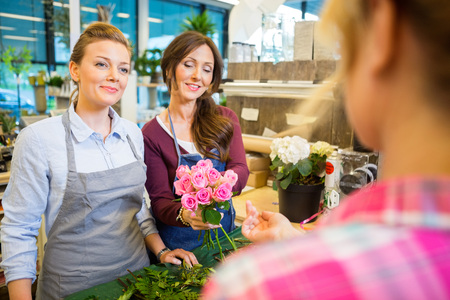 selling service smile: Happy florists selling rose bouquet to customer in flower shop