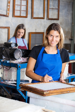 deckle: Portrait of happy female worker using tweezers to clean paper on mold in factory