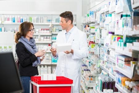 La metà degli adulti cliente femminile comunicare con il farmacista di sesso maschile nel corso farmaci a farmacia photo