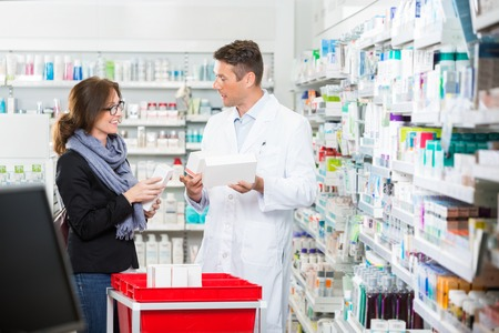 estanterias: Mediados de adultos cliente femenino que comunica con farmacéutico de sexo masculino sobre medicamentos en la farmacia