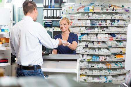 Smiling mature female chemist giving product to male customer in pharmacy