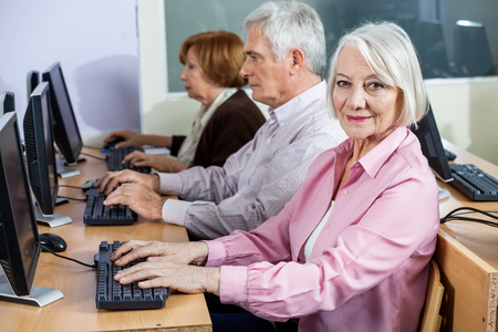 internet class: Portrait of smiling senior woman sitting in computer class with classmates at desk Stock Photo