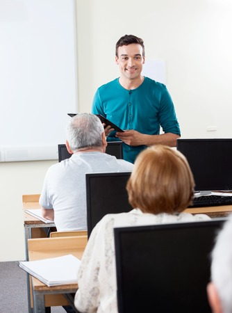 compute: Male teacher giving lessons to senior students in compute lab Stock Photo