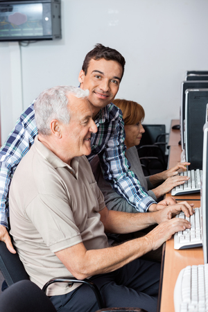 the elderly tutor: Male tutor helping senior man in using computer at classroom