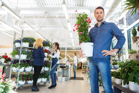 salesgirl: Portrait of confident man holding flower plant with salesgirl assisting customer in background at shop