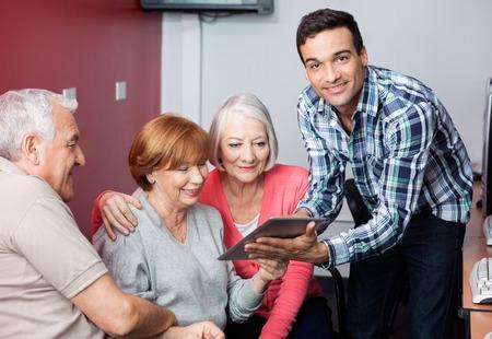 senior men: Portrait of happy tutor guiding senior students to use digital tablet in classroom