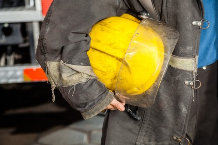 midsection: Midsection of female firefighter holding yellow helmet at fire station