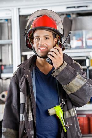 Giovane pompiere maschio in cerca di distanza durante l'utilizzo di walkie-talkie alla stazione di fuoco photo