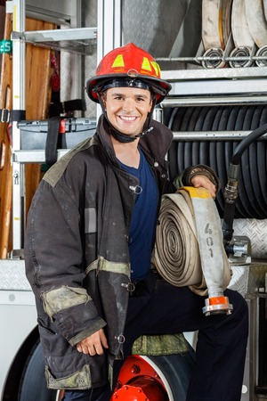 fireman helmet: Portrait of happy young fireman holding hose while standing by truck at fire station
