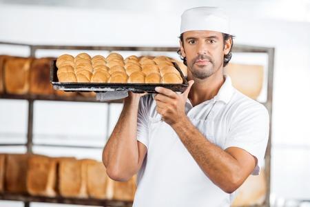 shoulder carrying: Portrait of confident male baker carrying baking tray on shoulder at bakery