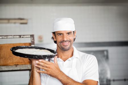 panadero: Retrato de la sonrisa panadero de sexo masculino que sostiene la bandeja de masa en la panadería