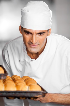 panino: Mature male baker looking at freshly baked breads in baking tray at bakery