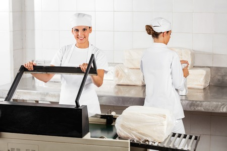 food industry: Portrait of confident female baker using vacuum seal machine while coworker working in bakery
