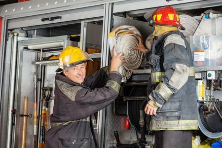 Ritratto di sorridere pompiere maschio assistere collega nella rimozione di tubo dal camion in caserma dei pompieri photo