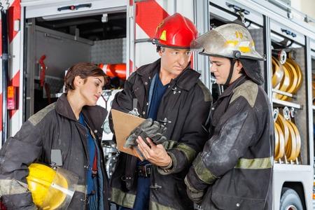 pompiere maschio che mostra appunti ai colleghi contro camion alla stazione di fuoco photo