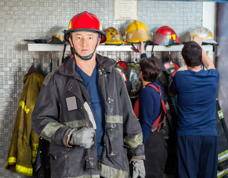 fire team: Portrait of confident mature fireman at fire station with team in background Stock Photo