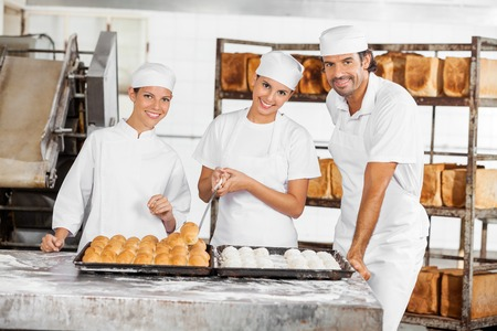 panino: Portrait of confident male and female Bakers standing at table in bakery Stock Photo