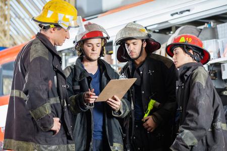 emergencia: bomberos masculinos y femeninos que leen el sujetapapeles junto al parque de bomberos Foto de archivo