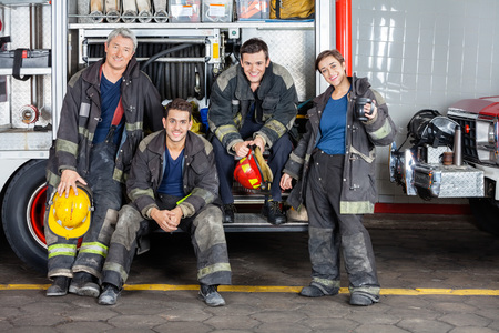 leaning on the truck: Full length portrait of confident firefighters by truck at fire station Stock Photo