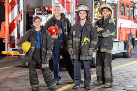 Ritratto integrale di vigile del fuoco in piedi sicuri contro camion alla stazione di fuoco photo