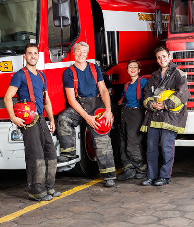 leaning on the truck: Portrait of smiling firefighters leaning on trucks at fire station Stock Photo