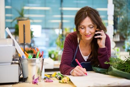 floristería mujer que usa el teléfono móvil mientras se escribe en el papel de tienda de flores Foto de archivo