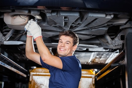 underneath: Portrait of smiling male mechanic working underneath lifted car at auto repair shop Stock Photo