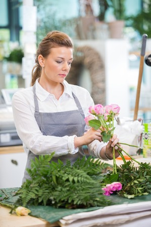 proprietor: Florist making rose bouquet at counter in flower shop Stock Photo