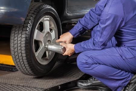 차고에 공 압 렌치와 남성 정비사 나사 자동차 타이어의 낮은 섹션