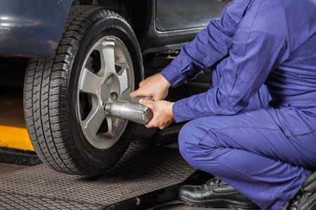 Low section of male mechanic screwing car tire with pneumatic wrench at garage Foto de archivo