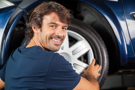 hubcap: Portrait of happy mechanic fixing hubcap to car tire at garage Stock Photo