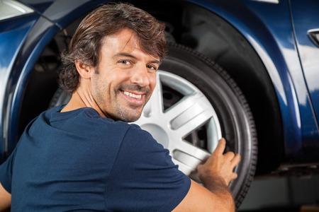 hubcap: Portrait of happy mechanic fixing hubcap to car tire at garage Stock Photo