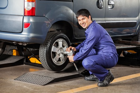 pneumatic tyres: Side view portrait of happy mechanic fixing car tire pneumatic wrench at garage