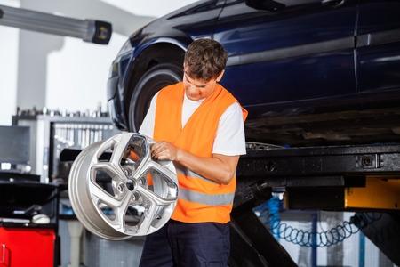 alloy: Male mechanic examining metallic alloy at auto repair shop