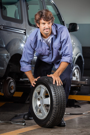 changing: Male mechanic holding car tire at auto repair shop