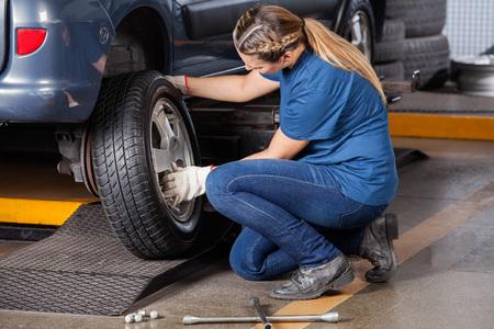 Vista laterale del meccanico femminile sostituzione della ruota auto al negozio di riparazione auto Archivio Fotografico