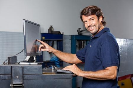 monitor de computadora: Retrato de monitor de la computadora hombre feliz mecánico de tocar en el taller de reparación de automóviles