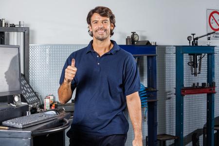auto repair: Portrait of happy mechanic gesturing thumbsup at auto repair shop